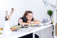 Молодой женский эскиз чертежа художника используя sketchbook с карандашем на ее рабочем месте в студии Портрет взгляда со стороны Стоковое фото RF