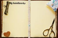 Sketchbook abierto con las herramientas de costura de la artesanía Fotografía de archivo libre de regalías