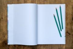 Sketchbook con le matite sulla tavola di legno immagine stock libera da diritti