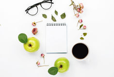 Sketchbook with cup coffee. Green apples with leaves, dry rose flowers and glasses. Flat lay, top view Stock Photography