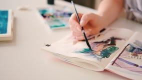 Sketchbook de la mano de las ilustraciones de la acuarela de la pintura del artista almacen de metraje de vídeo