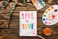 sketchbook with handlettering inscription `Love is love` on wooden table royalty free stock photography