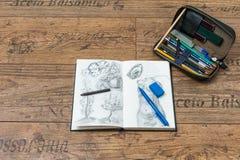 Sketchbook mit Anfängerbleistift-zeichnung und lederner Kasten des Bleistifts voll von Bleistiften Lizenzfreies Stockbild