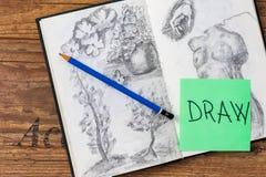 Sketchbook mit Bleistift und Zeichnungen und abgehobener Betrag simsen geschrieben auf Post-It Stockfoto