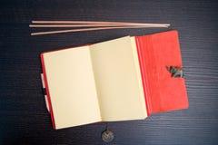 Sketchbook, Räucherstäbchen und Metallelefant Stockbilder