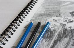Sketchbook with sketch and pen. Pencil-drawn sketch in sketchbook with three pencils Royalty Free Stock Photography