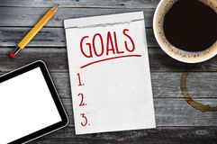 Sketchbook with tablet, pen, cup of coffee and personal goals checklist. On wooden background stock photography