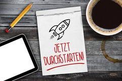 Sketchbook, Tablette, Tasse Kaffee auf einem hölzernen Schreibtisch mit den deutschen Wörtern für Anfang jetzt - jetzt durchstart lizenzfreie stockbilder