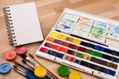 Sketchbook vacío en la tabla de madera con las fuentes del arte alrededor Mofa para arriba para el ejemplo o el arte Imagenes de archivo