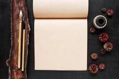 Sketchbooken och kineser borstar på den svart skrapade trätaen Arkivbilder