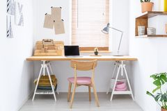 Sketchbooks and an open laptop on a wooden desk in a white, home office interior of a fashion designer. Real photo. royalty free stock photos