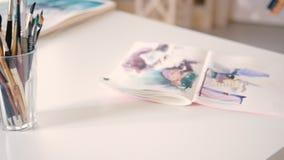 Sketchbooks ordenados de las brochas del lugar de trabajo del estudio del arte almacen de video