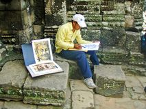 Sketching Angkor. Man sketching the faces of Bayon Temple in the Angkor Wat complex Stock Photography