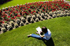 Sketching a flower bed. A young girl sits on the grass and sketches a flower from a flower garden Royalty Free Stock Photos