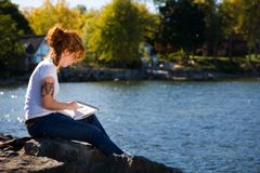 Sketching by the Lake. Young woman sketching at a lakeshore Royalty Free Stock Images