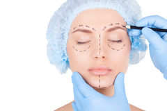 Sketching a patients face. Attractive young woman in medical headwear keeping eyes closed while doctor in blue medical gloves sketching her face isolated on Stock Photo
