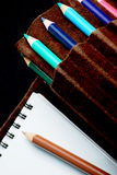 Sketchpad and colored pencils. A closeup of artist equipment, including a paper sketchpad and colored pencils, in an organizer or carrying case.  Black Stock Photography