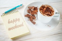 Sketchpad and a cup of hot cocoa. Sketchpad and cup of hot cocoa. Inscription in a notebook: Happy weekend Royalty Free Stock Photography