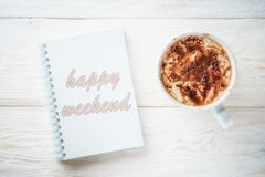 Sketchpad and a cup of hot cocoa. Sketchpad and cup of hot cocoa. Inscription in a notebook: Happy weekend Stock Photography