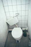 Skewed. An old toilet cistern with a crooked wall Royalty Free Stock Photos