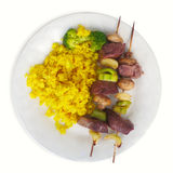 Skewer of beef cubes broccoli and rice white background plate yellow turmeric. Skewer of beef cubes turmeric rice and broccoli white plate Stock Photo