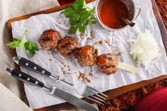 Skewer of beef or lamb kebab with spicy sauce on a wooden board stock image