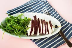 Skewer with beetroot and cheese, rucola. Sliced baked beetroot and cheese on skewer, rucola leaf on plate, dishtowel and fork on pink background Stock Image