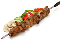 Skewer with shish-kebab and vegetables. Isolated, on a white background stock photography