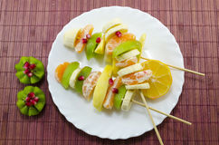 Skewered bananas, kiwis, oranges, lemons, pomegranate. Three skewers full of various fruit placed on a white plate royalty free stock images