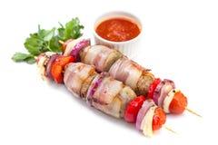Skewered nas salsichas de carne de porco saborosos das varas de madeira envolvidas com bacon Imagem de Stock