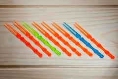 Skewers for canapes are multicolored, double on wooden background royalty free stock photo