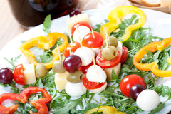 Skewers with cheese, mozzarella, olive, grape, tomato, on plate with fresh rocket Royalty Free Stock Photography