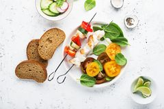 Skewers with chicken fillet, capsicum, zucchini, champignons and fresh colored tomatoes, spinach, cucumber, radish. Top. Skewers with chicken fillet, capsicum Royalty Free Stock Photos