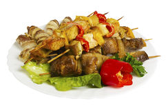 Skewers of chicken, pork, beef, lamb with greens on the plate, isolated Stock Images