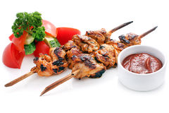 Skewers of chicken with vegetables. Cucumbers, tomatoes, cilantro and tomato sauce. Isolated on a white background stock photography