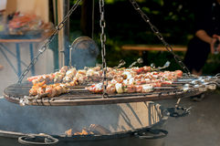 Skewers on the grill over the big pot Stock Image