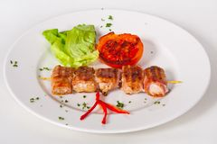 Skewers of grilled meat and vegetables on the white plate, Close up stock image