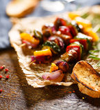Skewers of grilled meat and vegetables on a wooden table royalty free stock photo