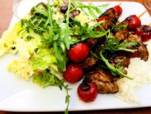 Skewers of lamb meat with Rice mixed salad tomatoes and tzatziki stock photography
