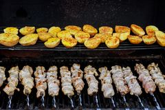 Skewers made from potatoes and meat as well as kebabs on the grill outdoors. Skewers made potatoes and meat as well as kebabs on the grill outdoors stock images