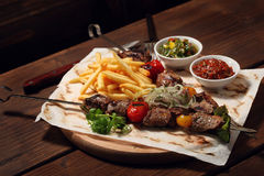 Skewers of Meat with sauce and potatoes fries on wooden cutting Royalty Free Stock Photography