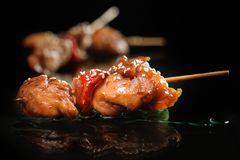 Skewers of meat and vegetables on the grill on a dark background. stock photo