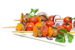 Skewers of meat with vegetables on a plate close-up Royalty Free Stock Images