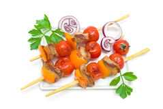 Skewers of meat with vegetables on a plate  on a white Stock Images