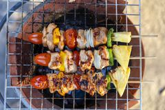 Skewers with pieces of grilled barbecue, green bell pepper, red tomato and meat for sell in street market, Thailand, closeup. Skewers with pieces of grilled stock image