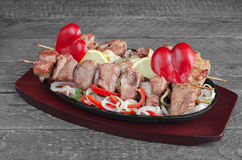 Skewers of pork, with a slice  lemon  salad  sweet peppers and onions. Royalty Free Stock Image