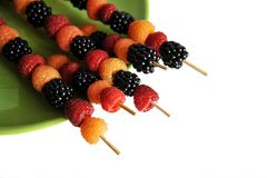 Skewers of raspberry berries of different colors on a green plate on a white royalty free stock images
