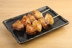 Skewers of roasted bonito tuna on black plate on wooden table Royalty Free Stock Photo
