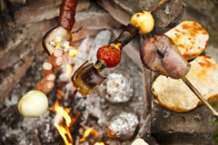Skewers rosting on camp fire. Royalty Free Stock Photography
