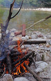 Skewers of sausages cooked in the bonfire on the banks of the Ri Royalty Free Stock Images
